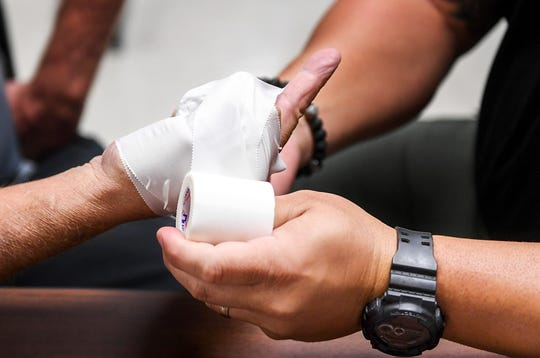 Tape is wrapped around fingers of a trainee to simulate missing fingers during a Tactical Medical for First Responders training, Tuesday, October 2.