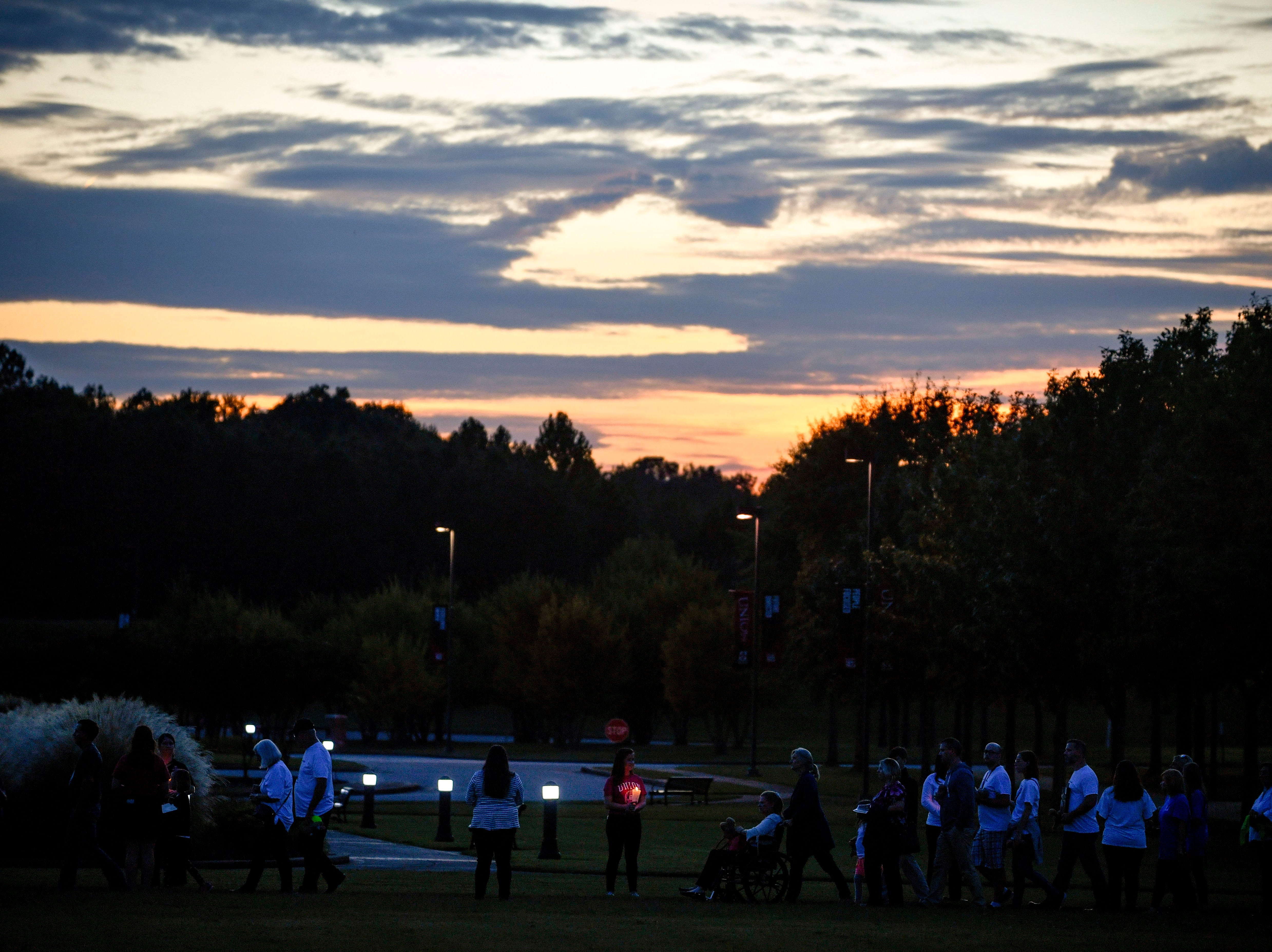 Attendees walk between Union University students holding a candlelight vigil during the annual Remember Me Walk hosted at Union University in Jackson, Tenn., on Monday, Oct. 1, 2018.