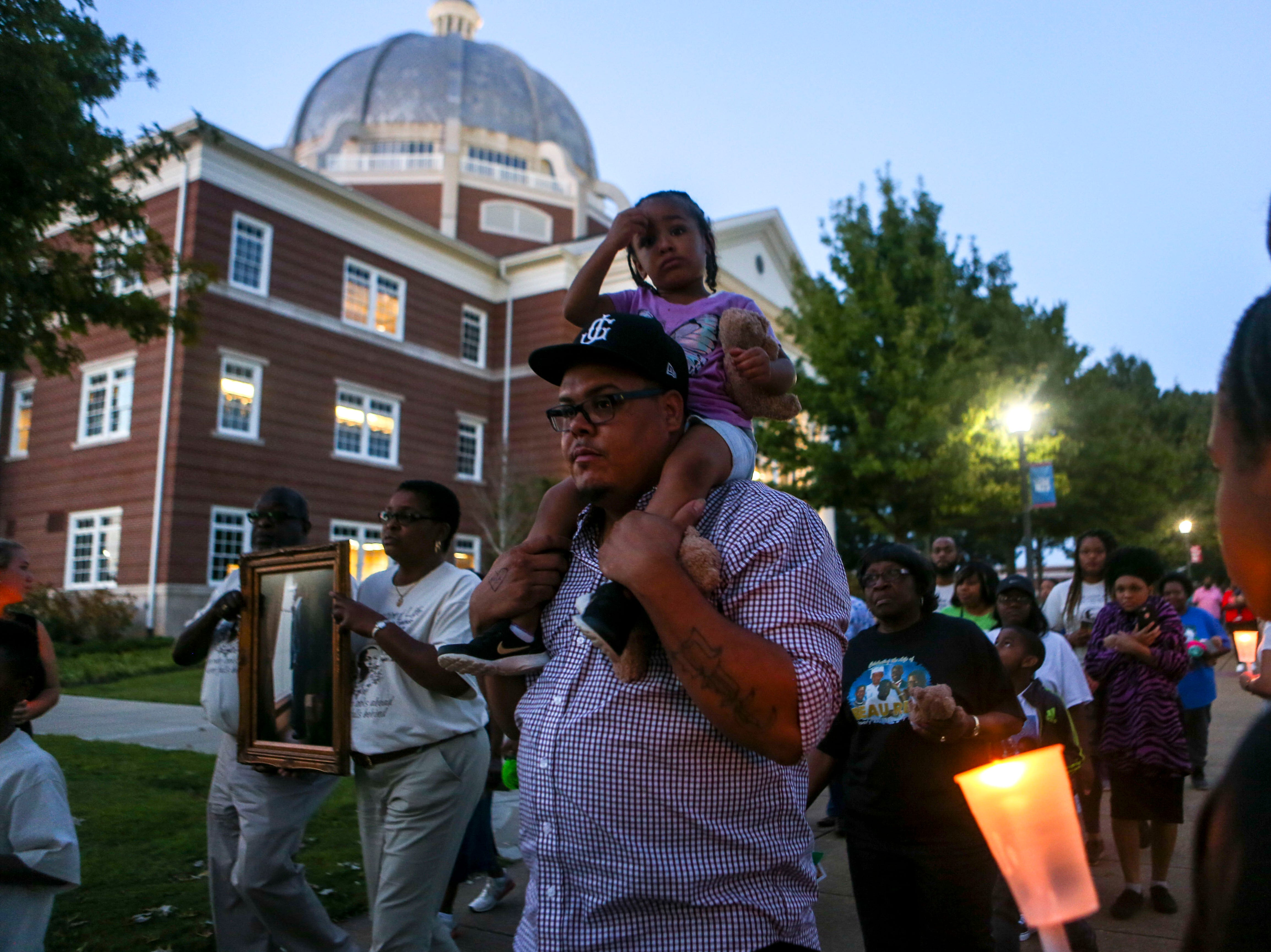 Attendees of the event walk through a vigil path flanked by Union University students with candles during the annual Remember Me Walk hosted at Union University in Jackson, Tenn., on Monday, Oct. 1, 2018.