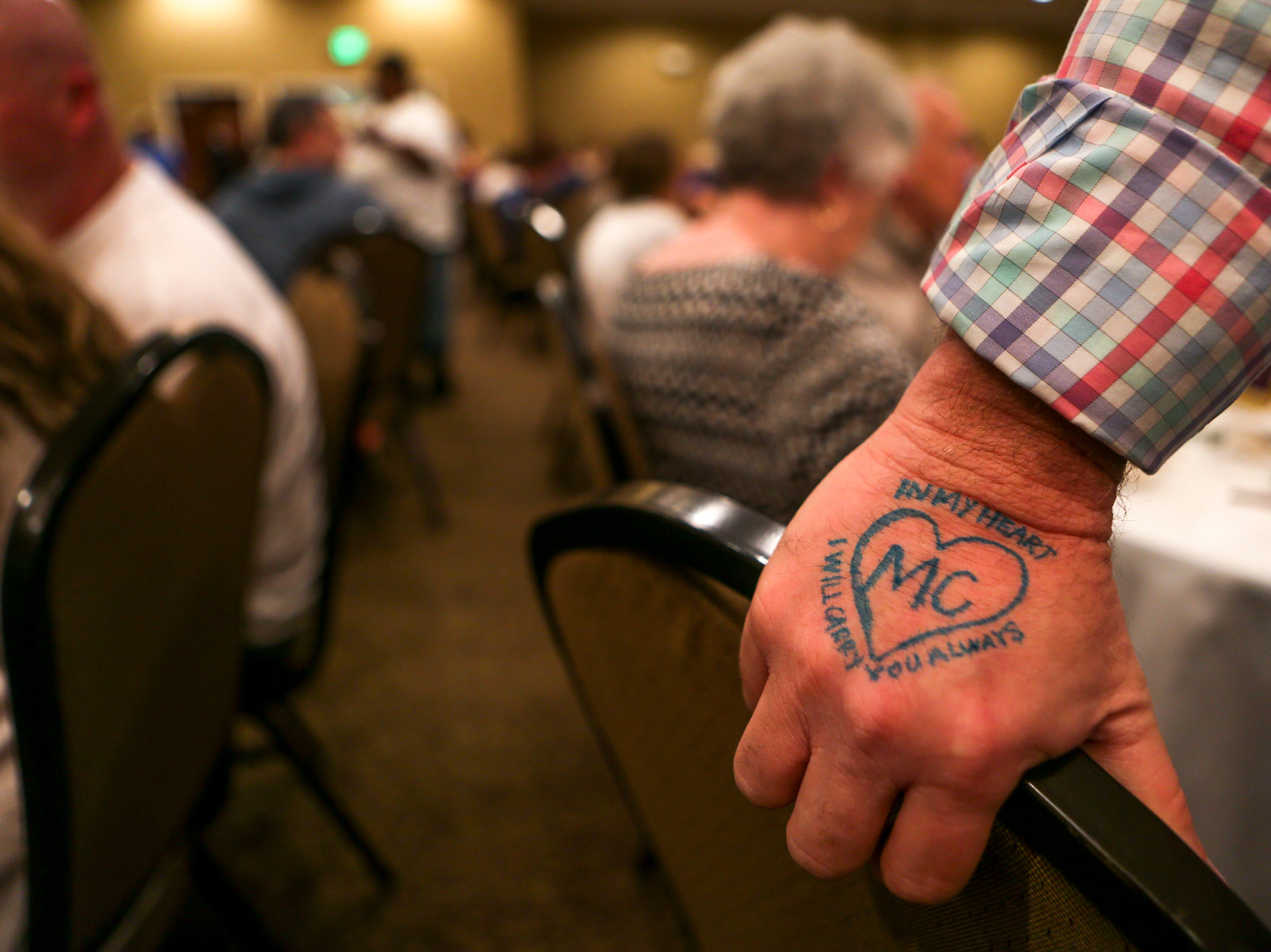 Steven Lee White, with a drawing to memorialize his daughter on his hand, braces himself on a chair during the annual Remember Me Walk hosted at Union University in Jackson, Tenn., on Monday, Oct. 1, 2018.