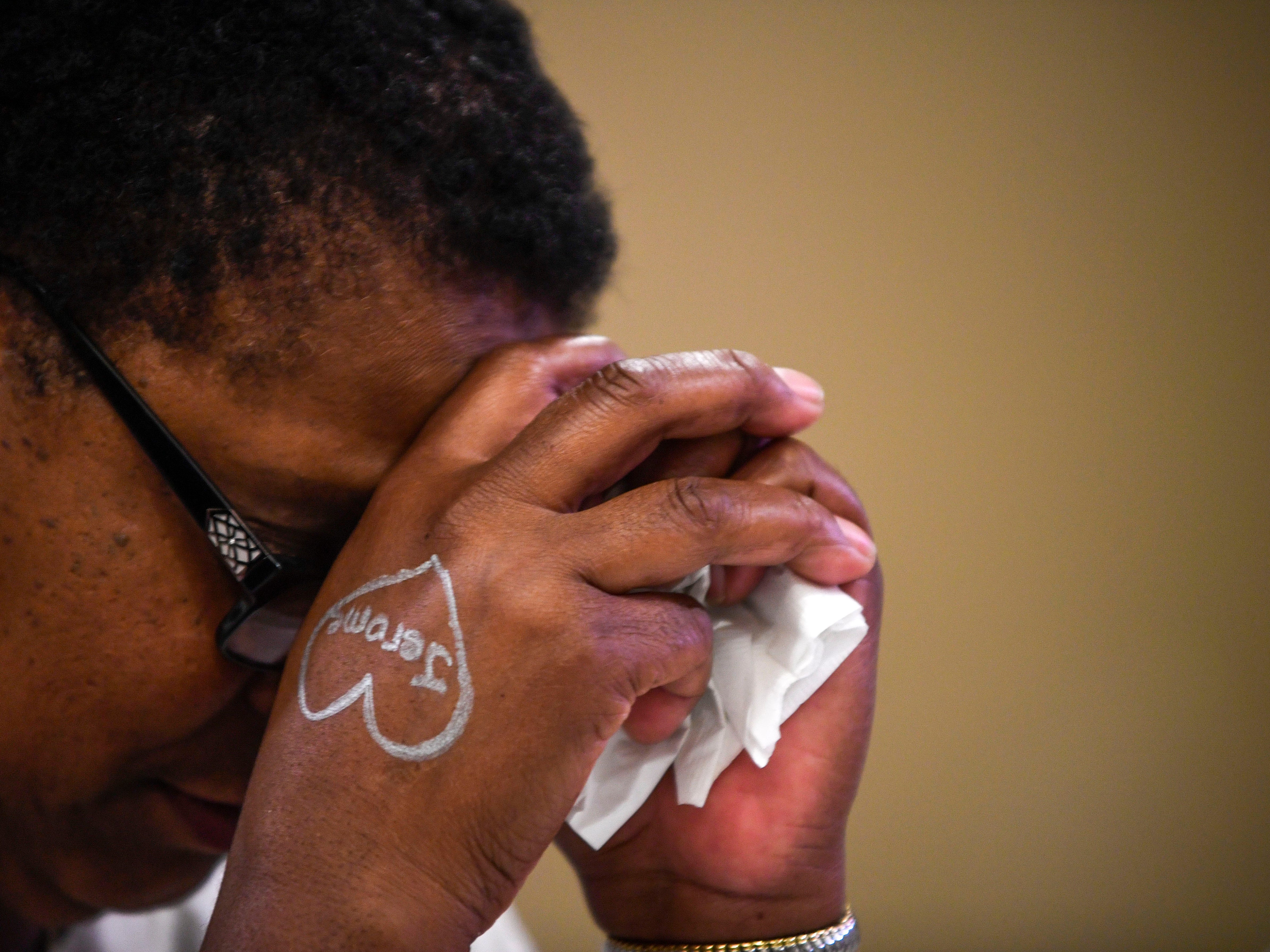 Norma Ellington bows her head for a prayer during the annual Remember Me Walk hosted at Union University in Jackson, Tenn., on Monday, Oct. 1, 2018. Ellington has attended the walk ever since she lost her son, Jerome, ten years ago.