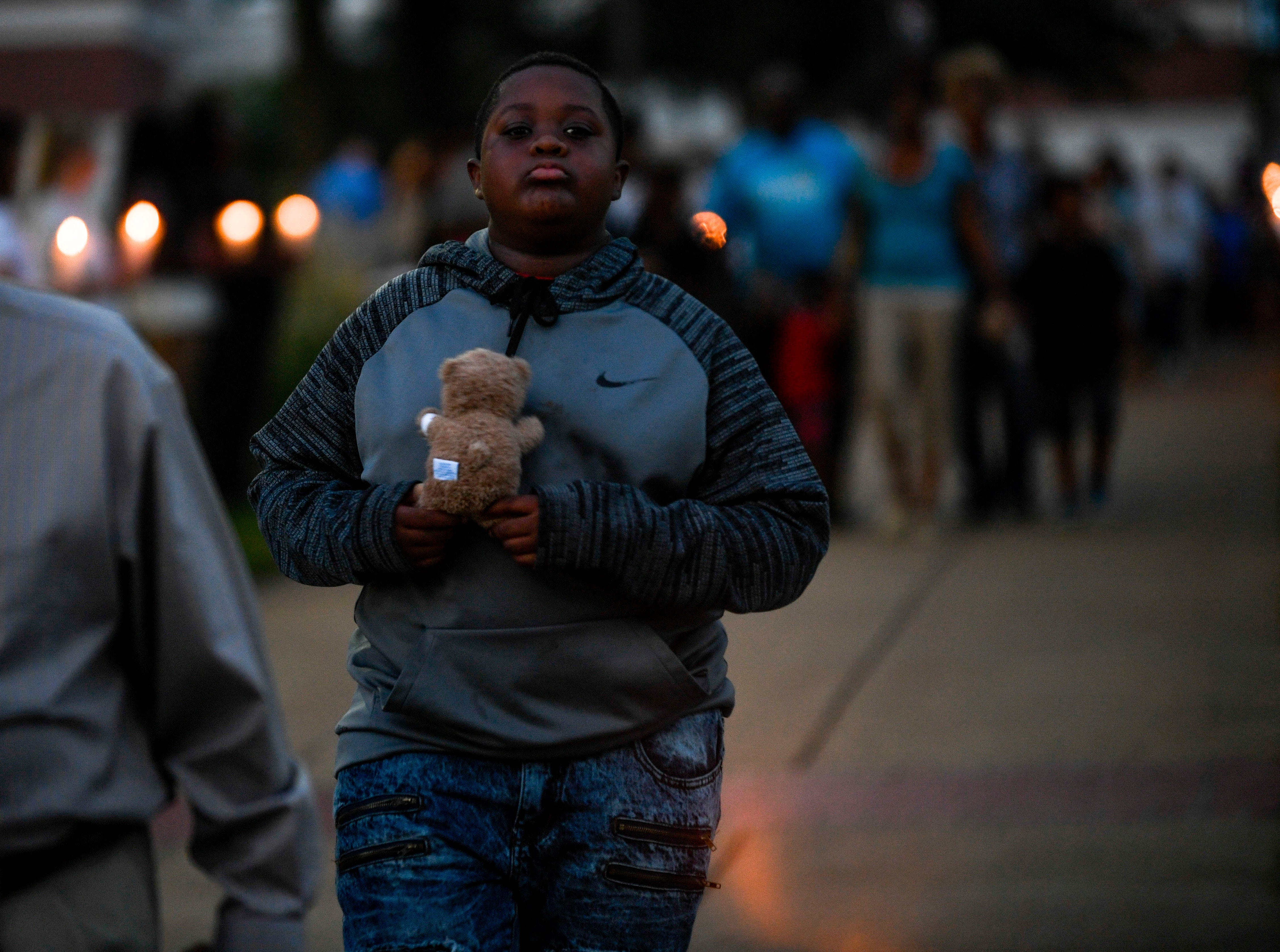 Attendees hold stuffed bears and walk between Union University students bearing candles during the annual Remember Me Walk hosted at Union University in Jackson, Tenn., on Monday, Oct. 1, 2018.
