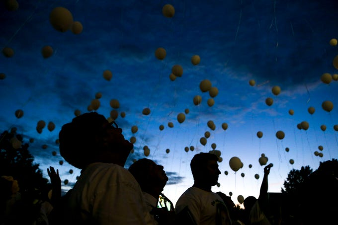 Attendees look to the sky as they release balloons to memorialize and say aloud the names of victims of violent deaths during the annual Remember Me Walk hosted at Union University in Jackson, Tenn., on Monday, Oct. 1, 2018.