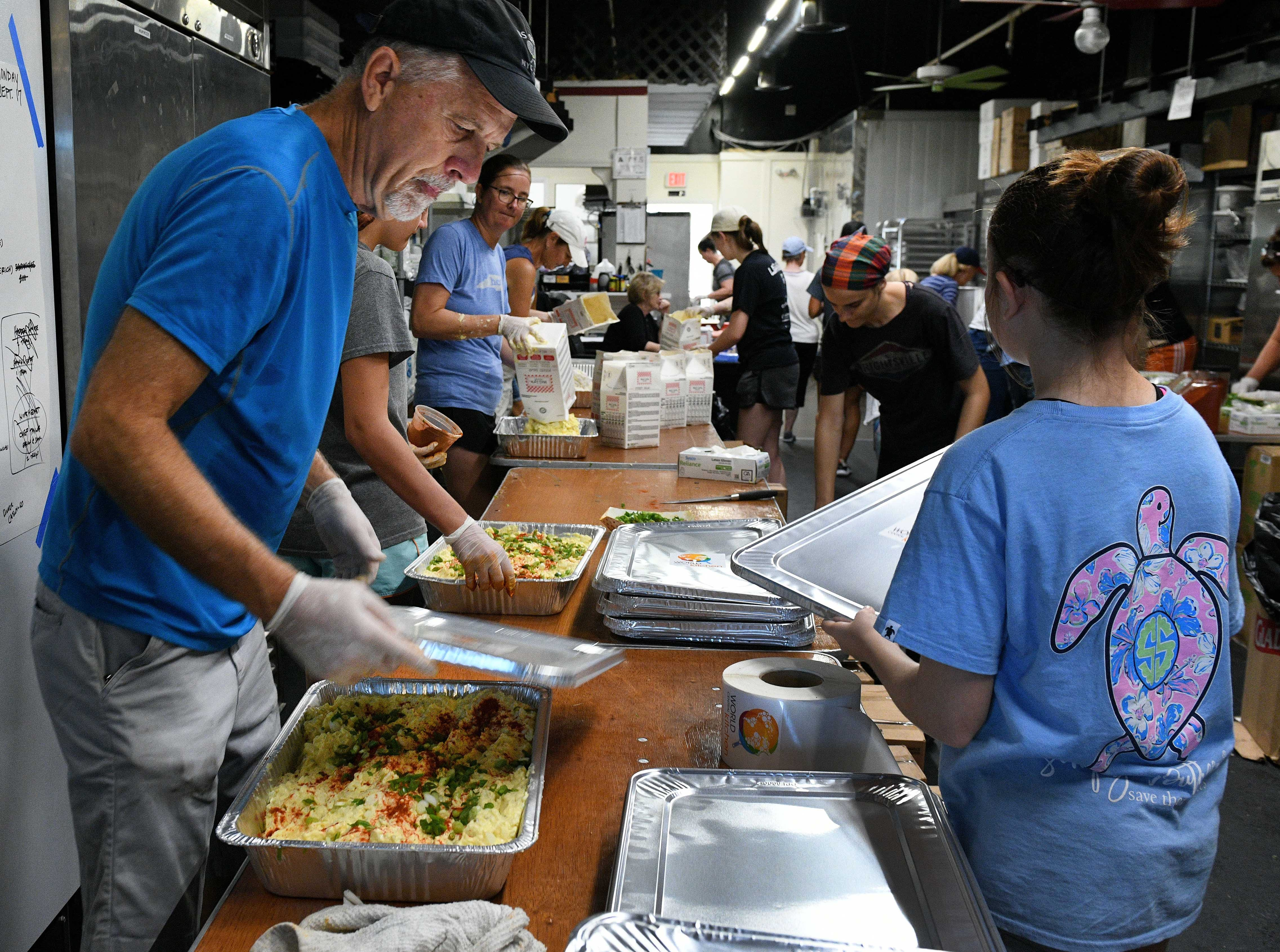 Gary Miller, World Central Kitchen volunteer, seals meals at their relief operation in Wilmington Wednesday, September 19, 2018. Volunteers have prepared over 120,000 meals so far following Hurricane Florence.