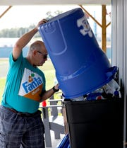 Kenny Gregg pours plastic bottles into a container Monday, Oct. 1, 2018, at the Fairfield Area Humane Society in Lancaster. Gregg started Kurbside with Kenny, a curbside recycling program in September.