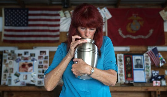 Dale Bozian kisses the urn that holds the ashes of her husband, Bruce, in the garage where he spent many hours tinkering with cars and motorcycles.  Many days Dale will talk to the urn or dance with it in the space where her husband spent many hours.