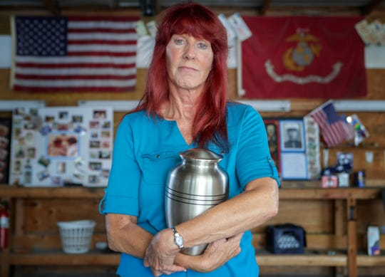 Dale Bozian holds the urn that holds the ashes of her husband, Bruce, in the garage where he spent many hours tinkering with cars and motorcycles.