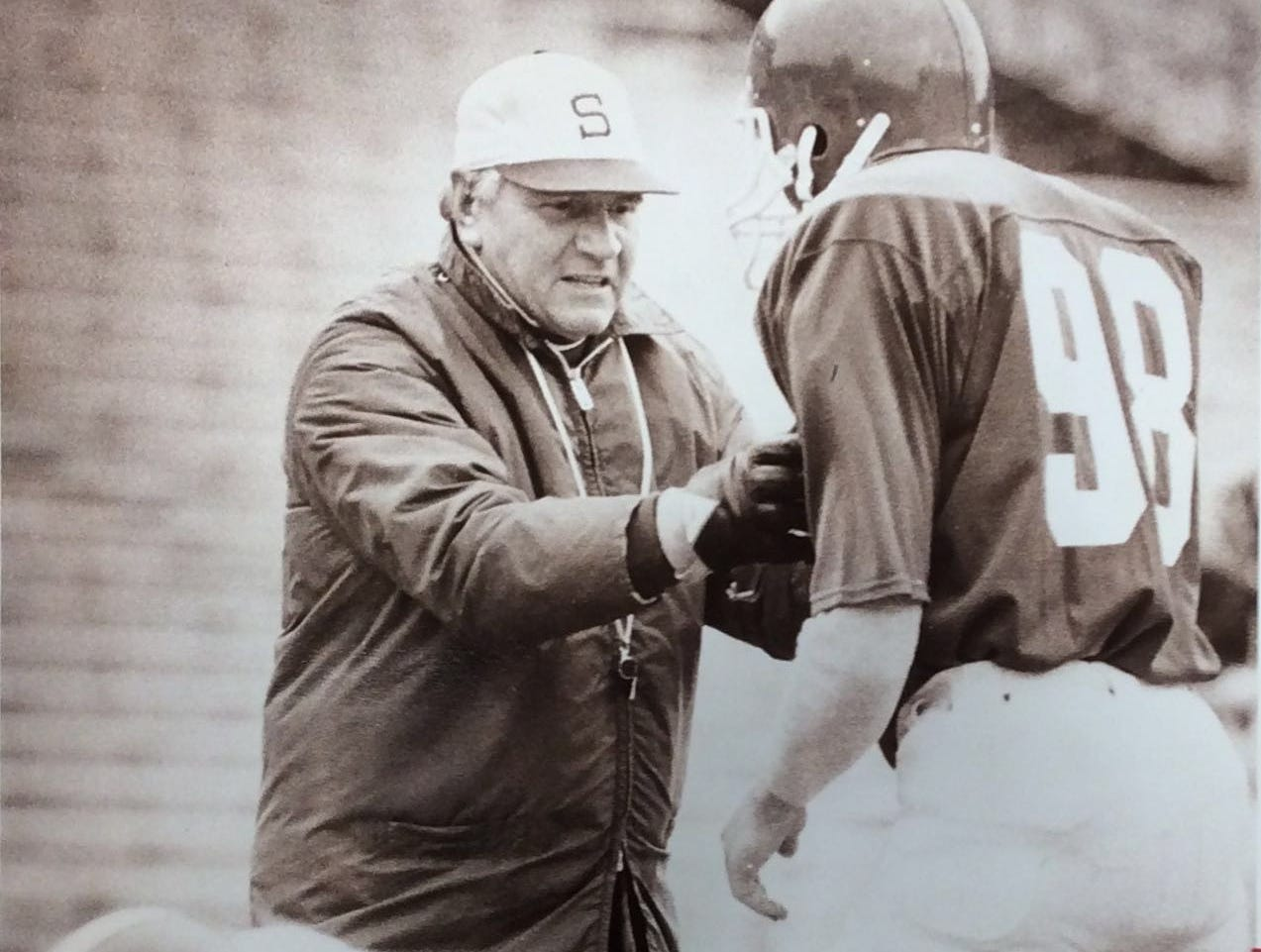 MSU Football Coach George Perles shows 98 how to position himself in a practice drill, undated photo.
