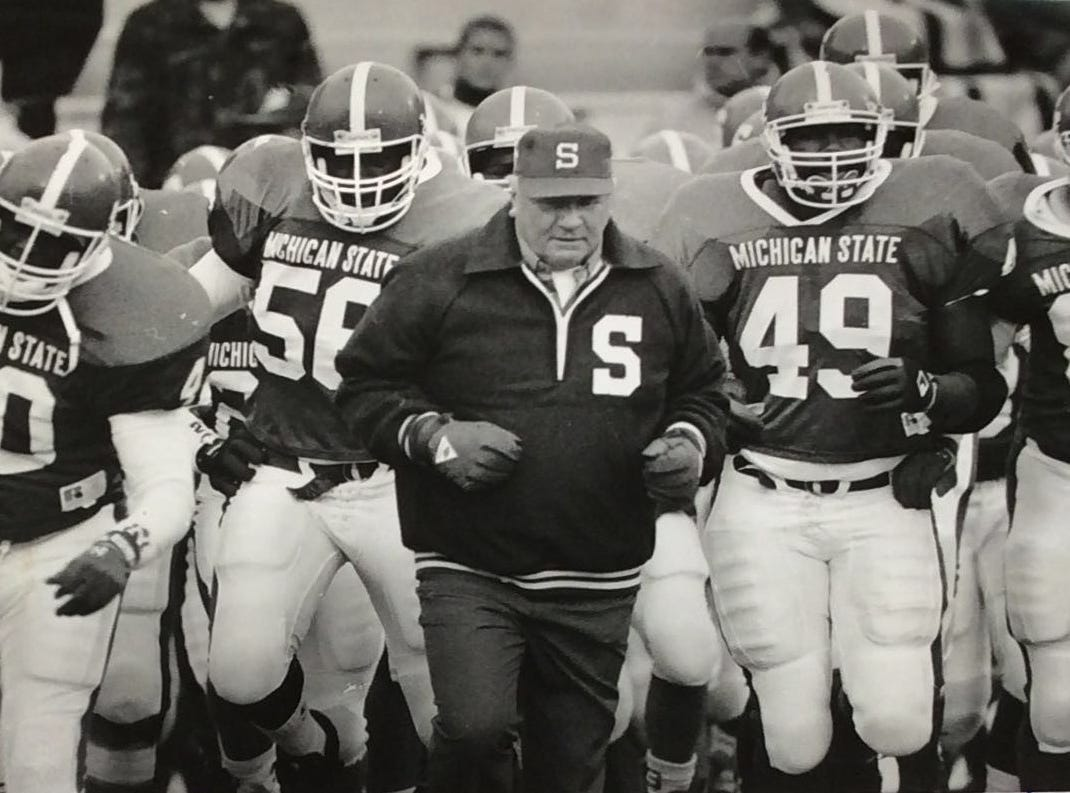 Michigan State University Football Coach George Perles leads his team out to the field, date unknown.