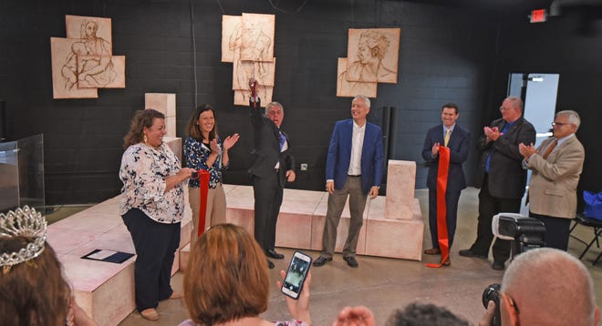 Rand Smith, president of the Renaissance Theatre's Board of Directors, holds ribbon cutting scissors high in the air after in celebration after cutting the ribbon to open the Renaissance Theatre's new performance space, Theatre 166 on Tuesday afternoon.