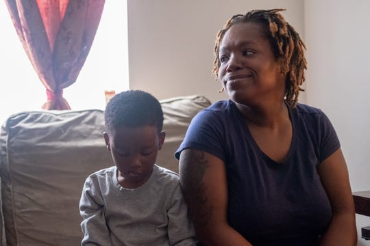 Shante Dennard, with her son Ja'Mykal, listens to Cassandra Ruffin during a home visit.