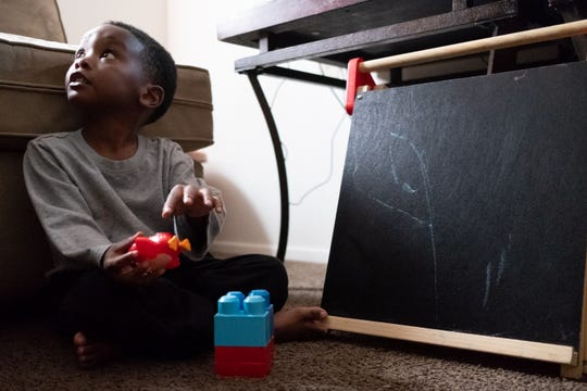 Ja'Mykal Dennard, 3, plays with toys during a home visit.