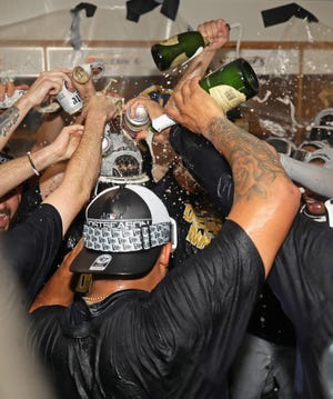Beer and champagne were flying as the Brewers celebrated winning the NL Central Division crown at Wrigley Field on Oct. 1.
