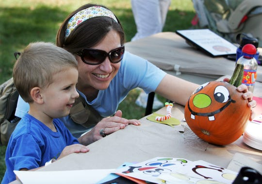 Luke Grove of Wauwatosa and his mother Sarah take a moment to admire the artwork on his pumpkin at the Boerner Botanical Gardens in 2011.