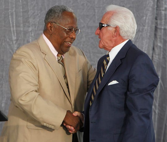 Baseball great Henry Aaron congratulates Milwaukee Brewers' radio announcer Bob Uecker on Aug. 31, 2012, during a dedication of the Bob Uecker bronze sculpture that will stand outside of Miller Park.