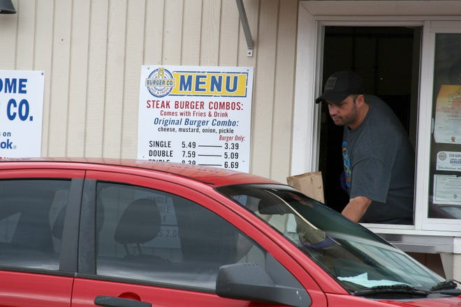 Robert Kotte, owner operator of Mtn. Home Burger Co., works the window of his burger stand. Each burger is grilled fresh at the time its ordered to ensure they are fresh and hot.