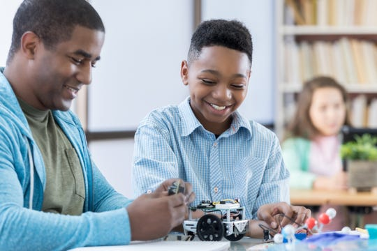 Male student enjoying time with mentor while building a robot together.