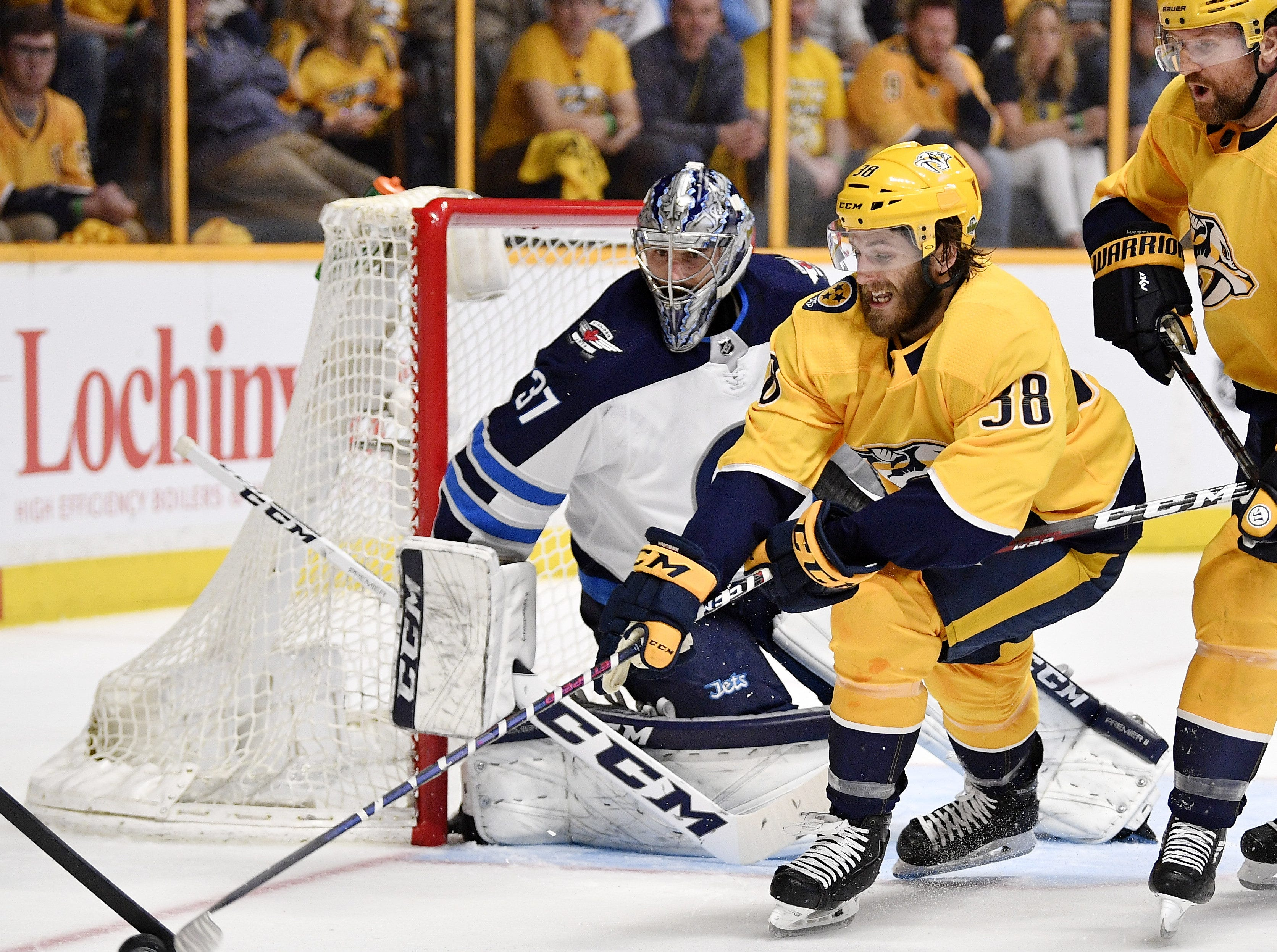 #38, Ryan Hartman, Forward - Nashville Predators right wing Ryan Hartman (38) plays the puck in front of Winnipeg Jets goaltender Connor Hellebuyck (37) during the first period of Game 7 of the second round NHL Stanley Cup Playoffs at Bridgestone Arena, Thursday, May 10, 2018, in Nashville, Tenn.