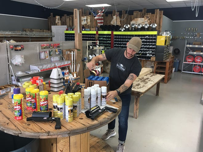 Sloan Mitchell, owner of The Tool Box Hardware Store in Fairview, organizes merchandise as stock is being liquidated in preparation for the store to close in mid-October.