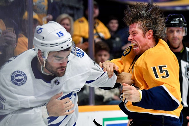 Predators forward Craig Smith (15) fights with Lightning center Andy Andreoff (15) during a preseason game Sept. 21 at Bridgestone Arena.