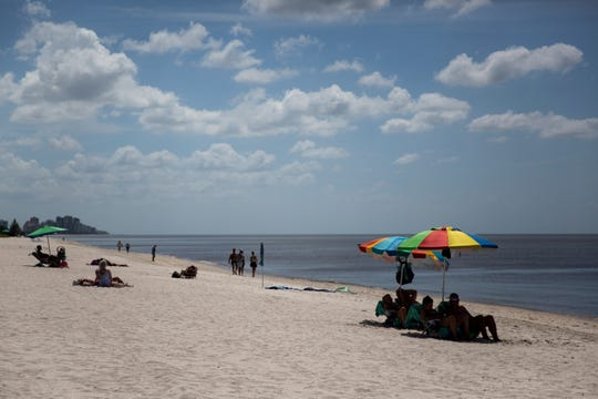 Beachgoers stay out of the water, which has turned a murky brown color due to an algal bloom, on Tuesday, October 2, 2018, at Vanderbilt Beach in Naples.