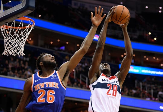 Washington Wizards center Ian Mahinmi (28), of France, grabs the ball against New York Knicks center Mitchell Robinson (26) during the first half of an NBA preseason basketball game, Monday, Oct. 1, 2018, in Washington.