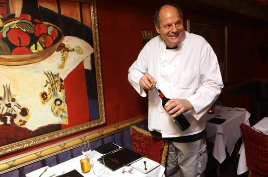 Peter Loria, chef and owner of Cafe Matisse, poses for a photo as he starts to open a bottle of wine with a cork screw. Thursday, Sept. 27, 2018