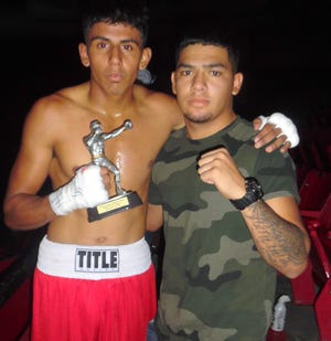 Jorge Madrid, left, won his 140-pound bout Saturday at the Clash of the Titans fight card in El Paso last weekend. Pictured with Madrid is stablemate Ruben Sanchez.