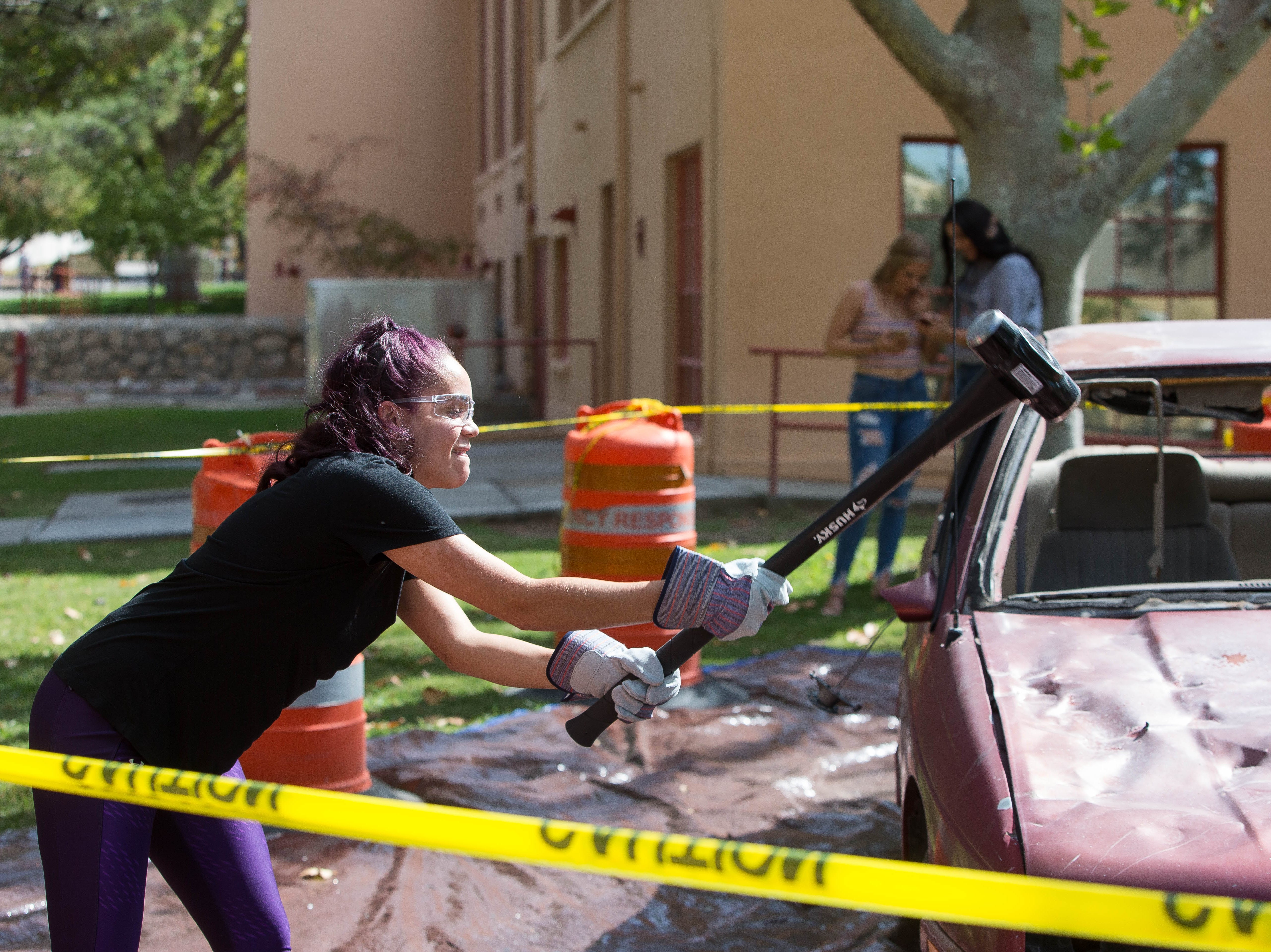 Alana Murphy, slams a sledgehammer into the hood of a car placed behind Milton Hall at New Mexico State University, Tuesday October 2, 2018. The opportunity to take out any stress on a car was set up as a fundraiser for the Aggie Cupboard. Students could pay with school supplies or 25 cents for one hit or $1 for four hits with a sledgehammer on the car.