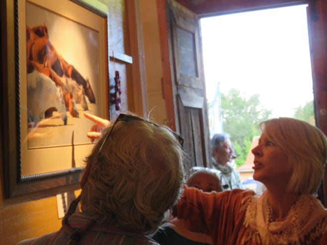 """At the opening reception, Barbara Mulleneaux, Purchase Prize Show judge, explains her reasons for selecting Laurie Ford's photography entry, """"The Watering Hole,"""" as the """"Best in Show"""" winner."""