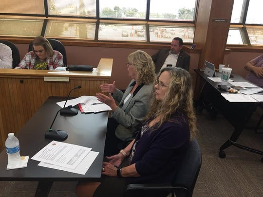 Eddy County Executive Administrative Assistant Gay West (left) and Human Resources Director Roxann Brannon talk about a position reclassification during the Oct. 2, 2018 Eddy County Board of Commissioners meeting.