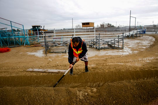 Alonzo Sloan works on a trench as workers prepare the rodeo ring for the Northern Navajo Nation Fair Tuesday at the fairgrounds in Shiprock.