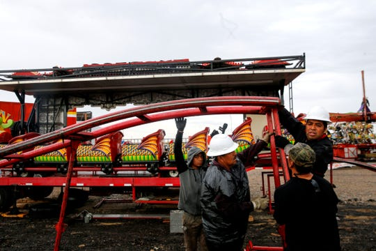 Workers assemble the track for a roller coaster Tuesday at the Northern Navajo Nation Fairgrounds in Shiprock.