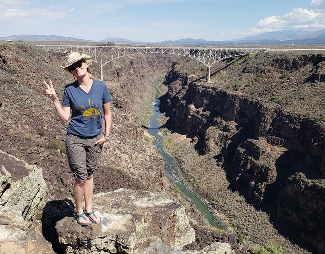Anna Dozier stands on the cliffs over seeing the Rio Grande Gorge River and Bridge in the background.