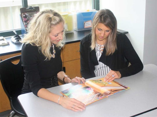"""NIcole Hicks (left), a language arts teacher at West Middle School, looks over the recently-released """"Construction Cousins"""" book with sister/collaborator Stacie Majszak, a counselor at Discovery Middle School."""