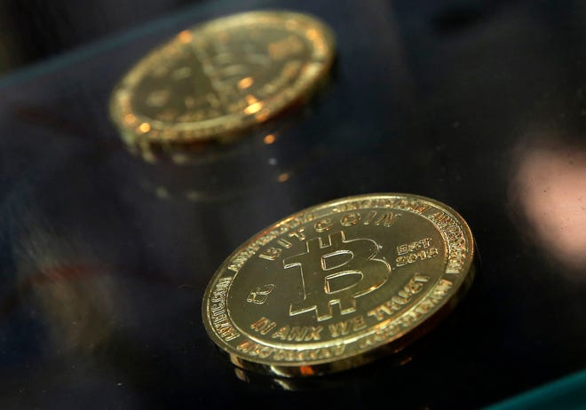 "FILE- In this Dec. 8, 2017, file photo, coins are displayed next to a Bitcoin ATM in Hong Kong. British lawmakers are urging regulation for cryptocurrencies such as bitcoin in a report that describes the current situation as the ""Wild West."" In a report Wednesday, Sept. 19, 2018 on digital currencies, Parliament's Treasury Committee called for regulations to protect consumers and prevent money laundering. (AP Photo/Kin Cheung, File)"