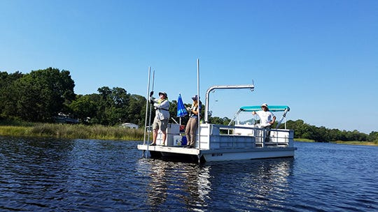 Water testing is conducted by Escambia County officials at Bayou Chico.