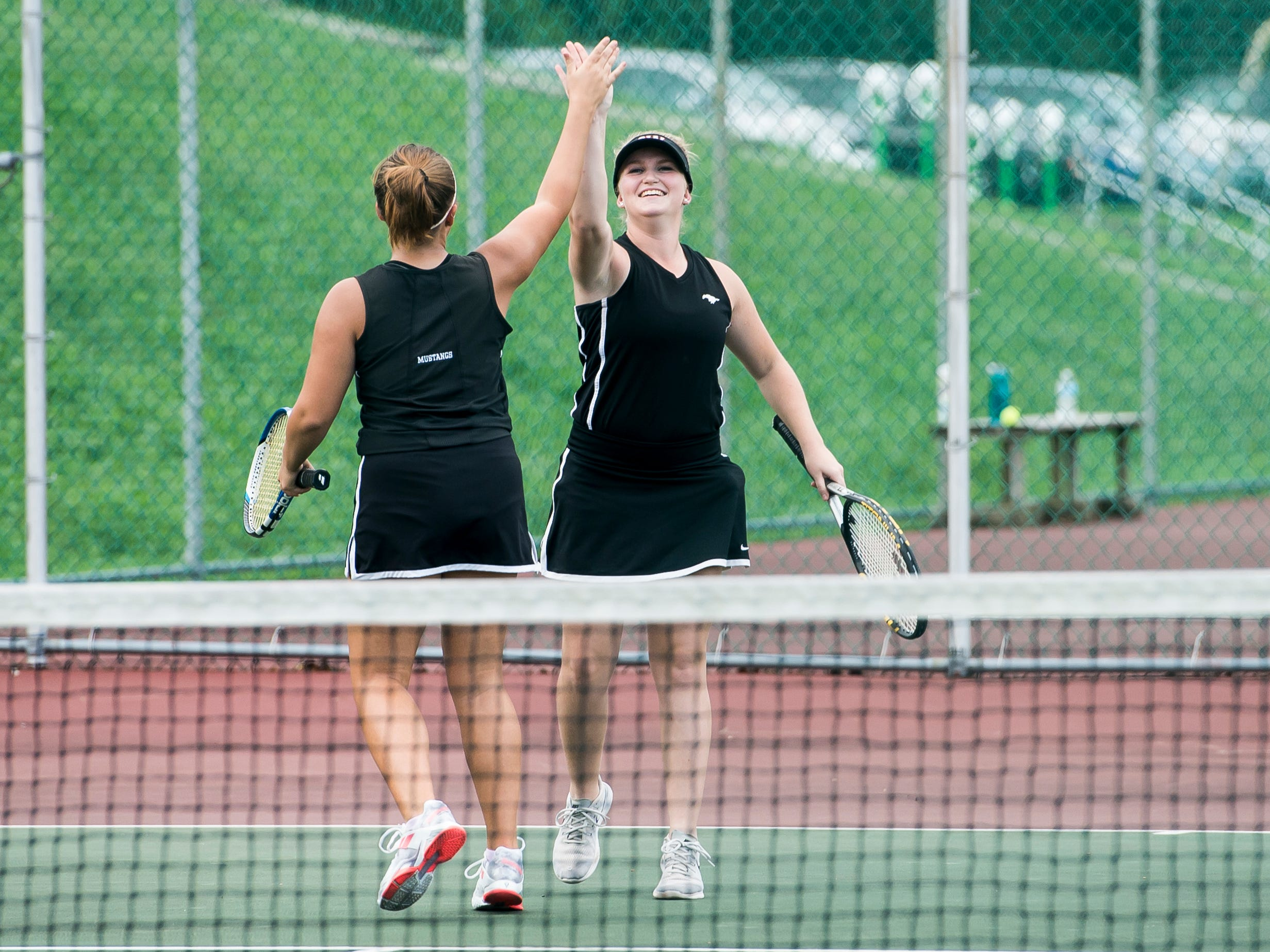 South Western's Sydney Zepp, right, and Sarah McComas, playing in the No. 1 doubles match, high-five after winning a point against New Oxford on Wednesday, September 26, 2018. The match had to be postponed due to rain and was finished on October 2.