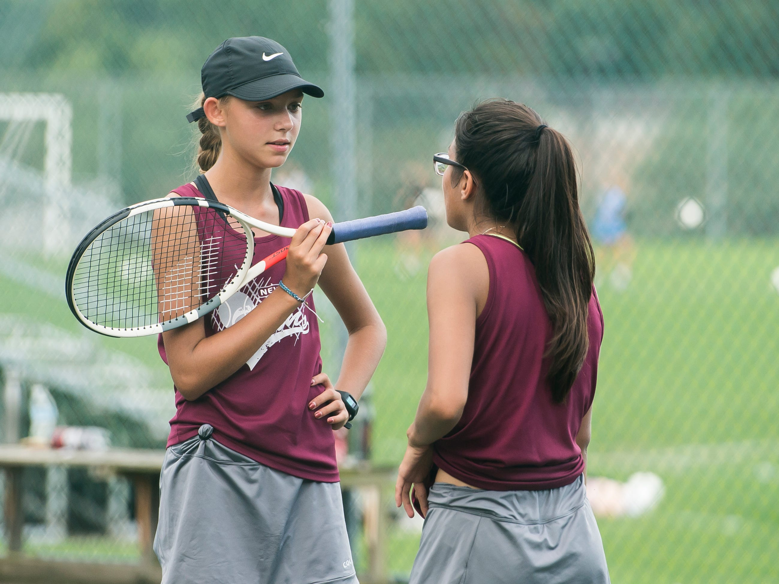 New Oxford's Kayla Hoffman, left, and Anallely Rugerio-Soto talk between sets while playing in the No. 2 doubles match against South Western on Wednesday, September 26, 2018. The match had to be postponed due to rain and was finished on October 2.