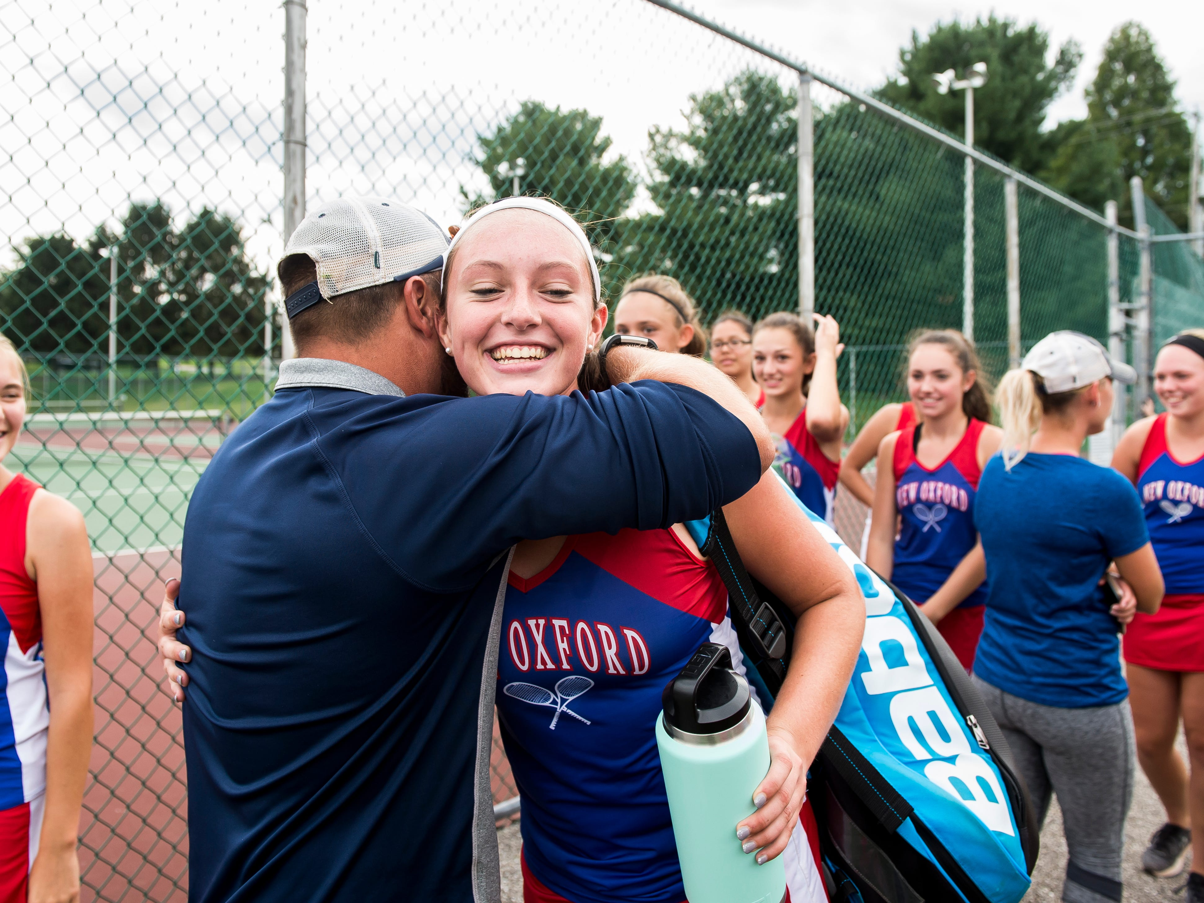New Oxford's Kasi Conjack gets a hug from head coach Travis Martin following her No. 2 singles win against South Western on October 2, 2018.