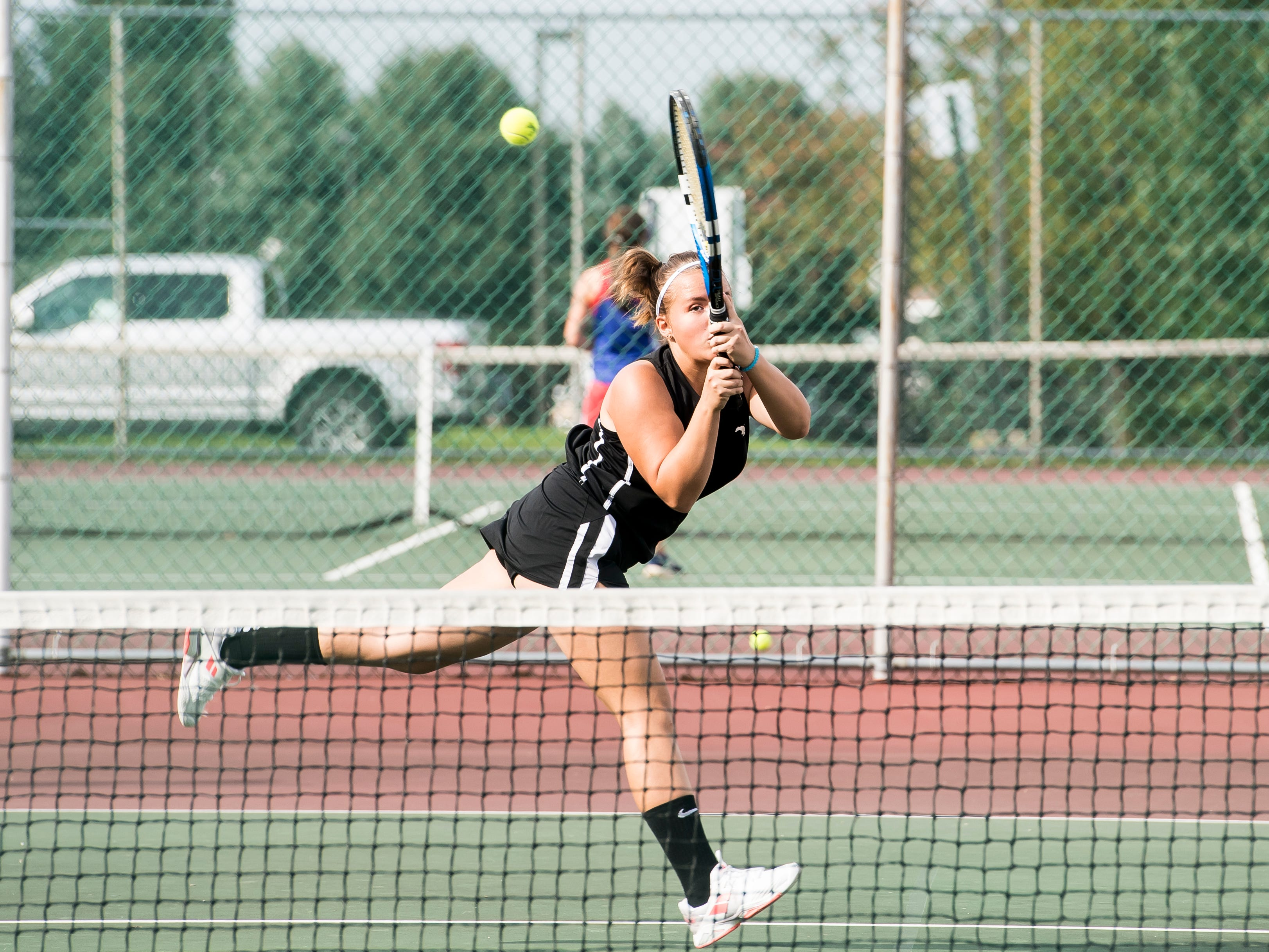 South Western's Sarah McComas follows through on a swing while playing in the No. 1 doubles match against New Oxford on Tuesday, October 2, 2018.