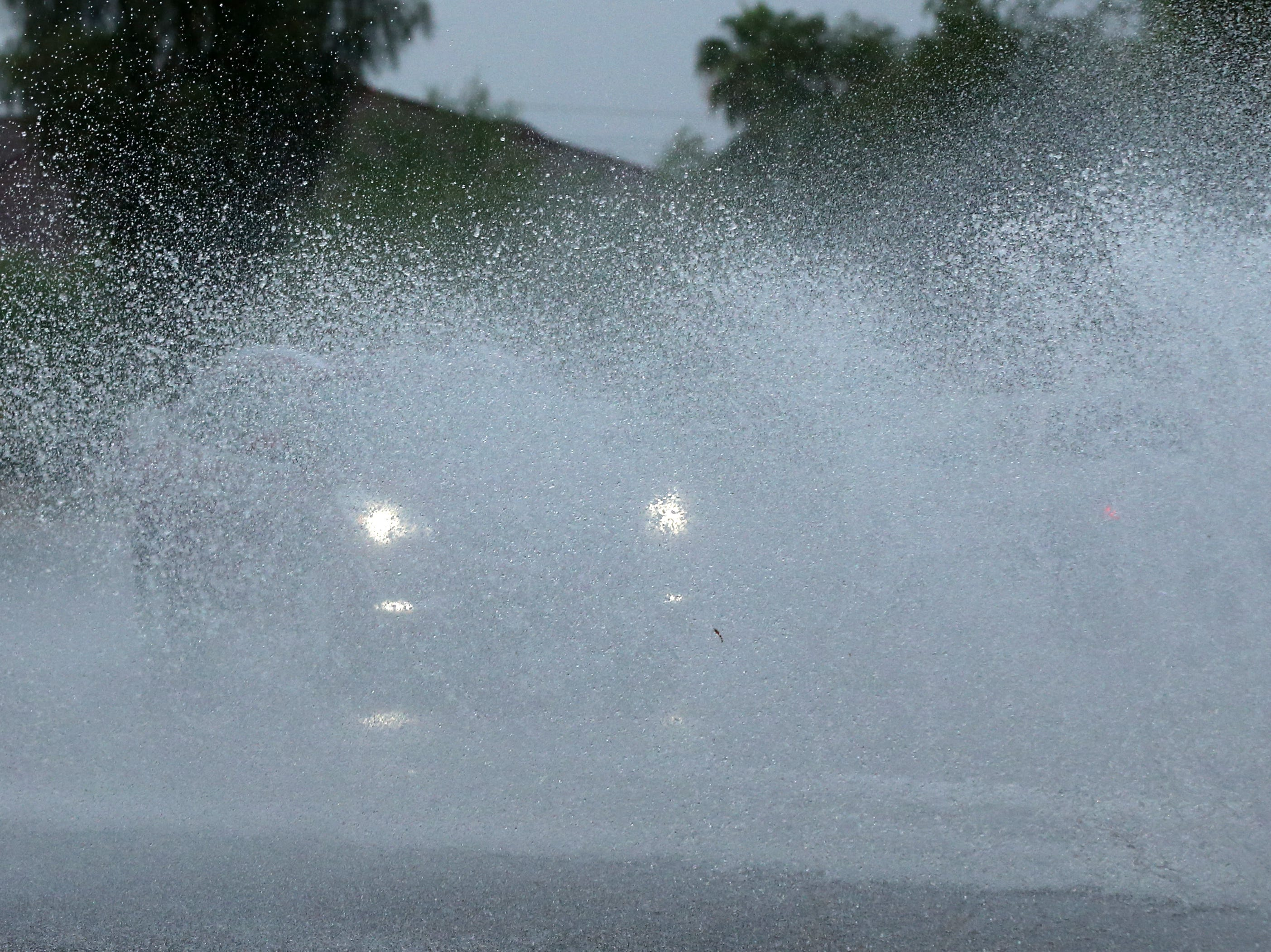 Cars drive through rain on 32nd Street north of Cactus Road in Phoenix. The remnants of Hurricane Rosa is bringing heavy rain to central Arizona.