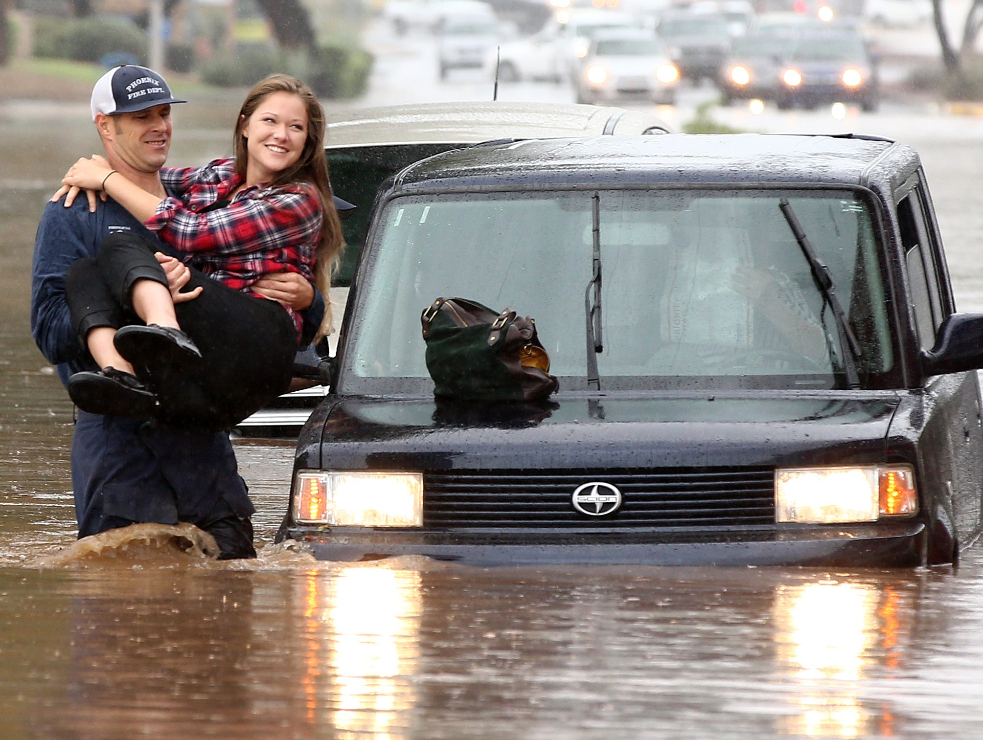 A Phoenix firefighter carries a motorist from her car after being caught in flood waters that covered Tatum Blvd. north of Shea Boulevard in Phoenix. The remnants of Hurricane Rosa is bringing heavy rain to central Arizona.
