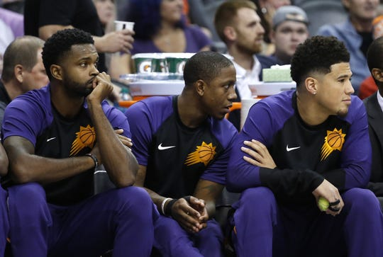 Suns Troy Daniels (L-R), Isaiah Canaan and Devin Booker watch the team from the bench during the first half at Talking Stick Resort Arena in Phoenix, Ariz. on October 1, 2018.