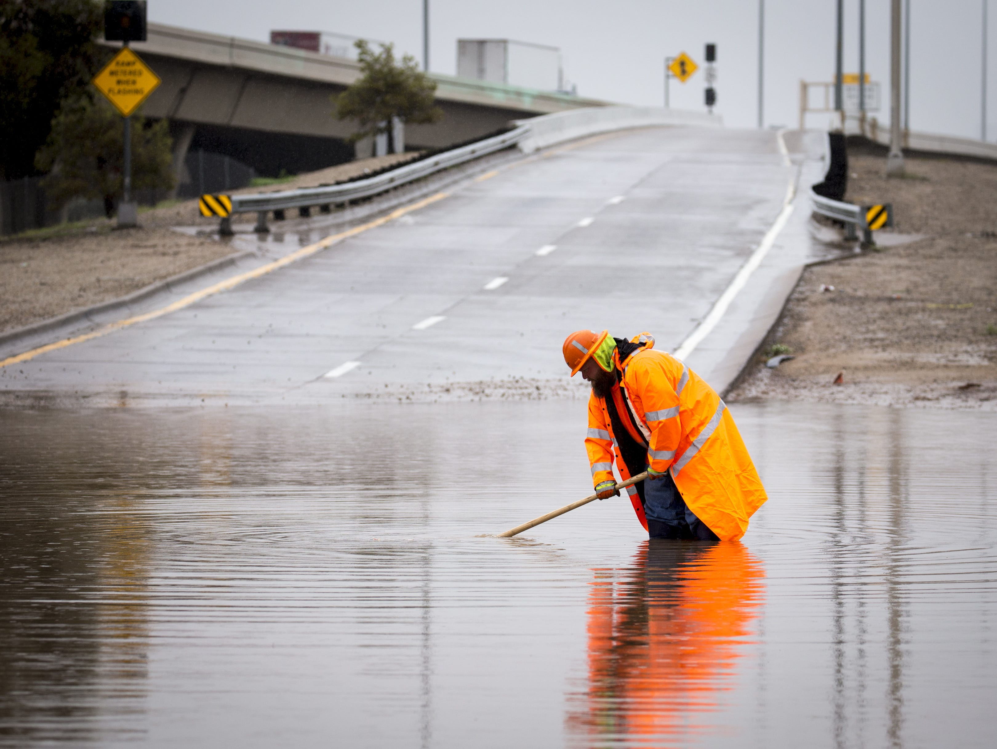 Mike Culp from the Arizona Department of Transportation clears a drain on the closed I-10 on-ramp at 19th Avenue, Oct. 2, 2018, in Phoenix.