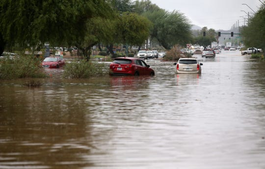 Cars are abandoned after Phoenix firefighters rescued motorists who were caught in flood waters that covered Tatum Boulevard north of Shea Boulevard in Phoenix on Oct. 2, 2018.