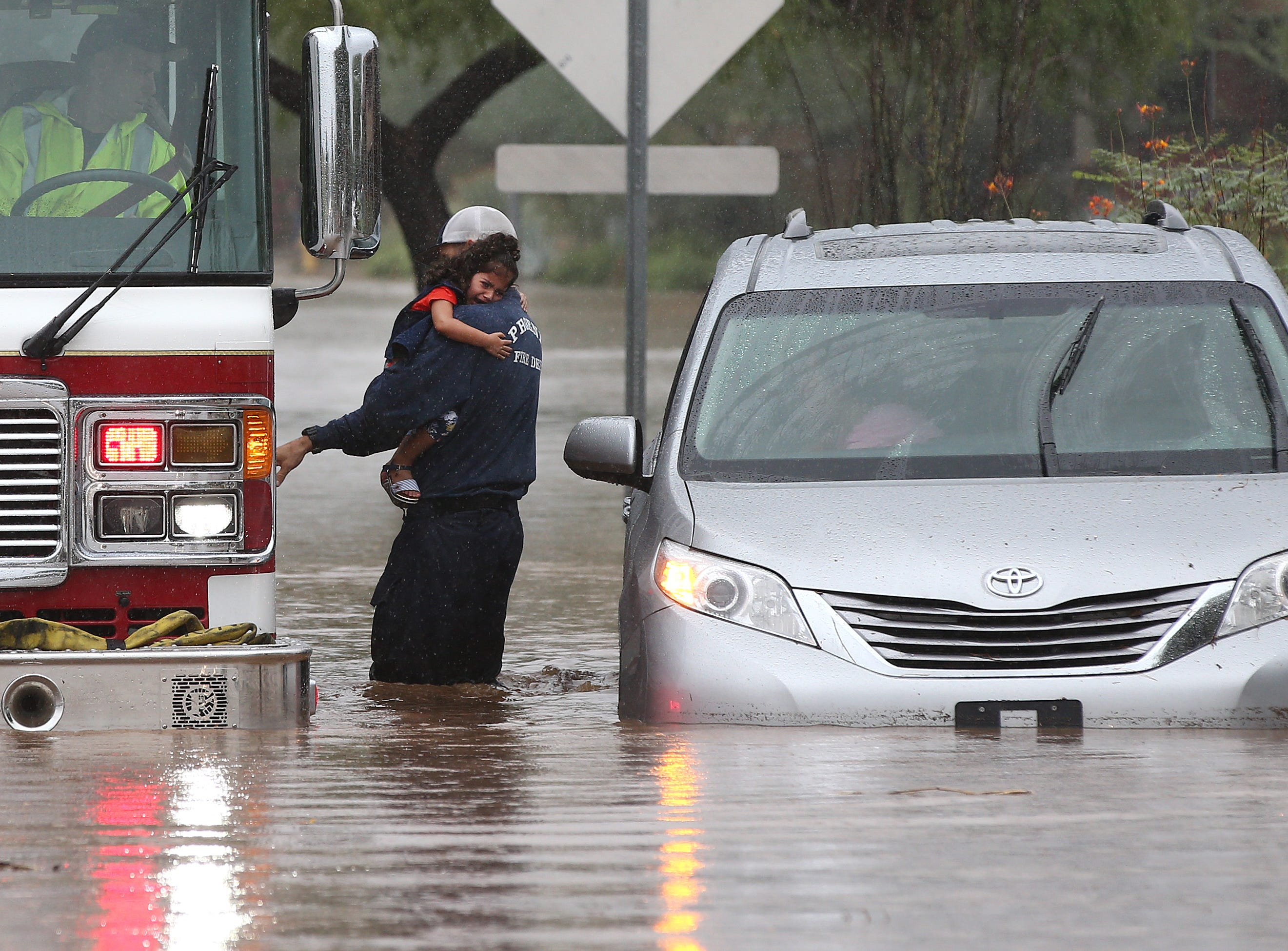 Phoenix Firefighter rescues a small girl from her van after being caught in flood waters that covered Tatum Boulevard north of Shea Boulevard in Phoenix. The remnants of Hurricane Rosa is bringing heavy rain to central Arizona.