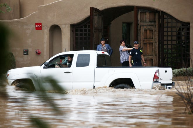 A Phoenix firefighter watches a motorist choosing to drive through flood waters that covered Tatum Boulevard north of Shea Boulevard in Phoenix on Oct. 2, 2018.