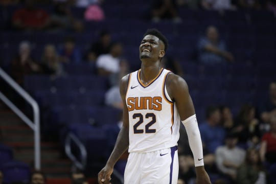 Suns' Deandre Ayton (22) limps as he walks down the court against the Kings during the first half at Talking Stick Resort Arena in Phoenix, Ariz. on October 1, 2018.