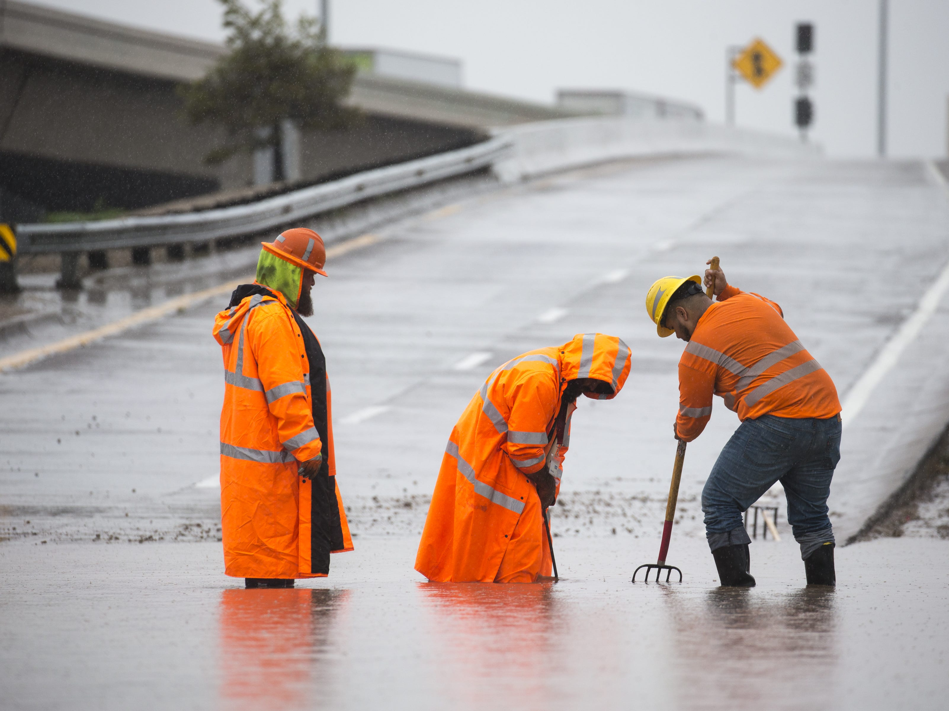 From left: Alan Garcia, Alex Munoz and Mike Culp, all with the Arizona Department of Transportation, clear a drain on the closed I-10 on-ramp at 19th Avenue, Oct. 2, 2018, in Phoenix.